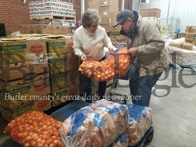 Peggy McCorkle and Bill Hilliard,  volunteers with the St. Vincent DePaul Food Pantry in Butler, lift a large bag of onions that will be divided among the boxes of food distributed to hundreds of needy families this holiday season. Photos by Paula Grubbs