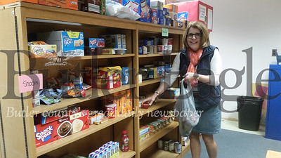 Maria Holl, a teacher at the South Butler Intermediate Elementary School and founder of the Weekend Food program,  packs food items into a bag on Friday for a needy student to take home.