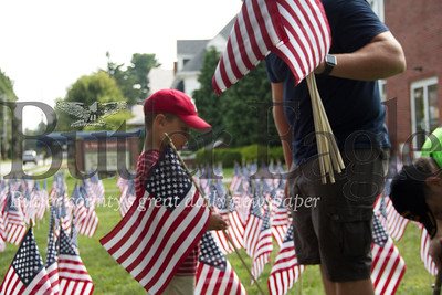 Leo Garing, left, helps Scott Frederick plant flags in St. Peter's Reformed Church in Zelienople on Aug. 31, 2018