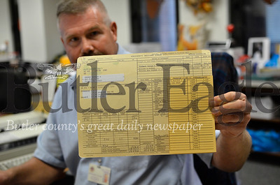 Christopher Savage, the county's assessment director, holds up one of thousands of paper property assessment records on file in the county courthouse. Tanner Cole / Butler Eagle