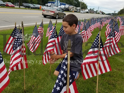 Connor places one flag in a memorial of 660 that represents the total number of veterans who die by suicide each month.