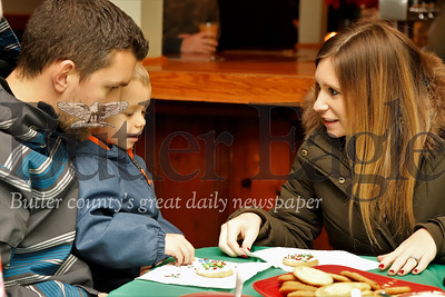 Brody Richards decorates a Christmas cookie with his mom Lindsay and dad Ryan at Shu Brew's Cookie Decoration with Mrs Claus Thursday night during Zelienople's Miracle on Main Street Christmas festival. Seb Foltz/Butler Eagle