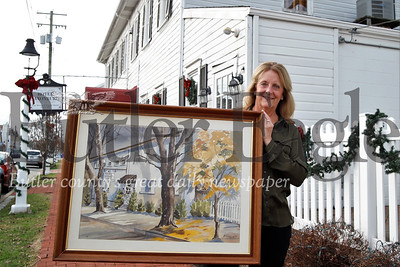 Hotel Saxonburg owner Judy Ferree shows the hotel painting originally commissioned by Fred Rogers. Seb Foltz/Butler Eagle