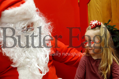 Preslie Everett-Pyle, 5, tells Santa what she wants for Christmas Saturday at Butler's Pancakes with Santa breakfast. Seb Foltz/Butler Eagle