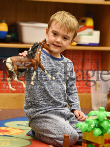 Harold Aughton/Butler Eagle: Jaxson Muller, 3, plays horses with his mother Julia in the Mars Library, Monday, Dec. 9, 2019