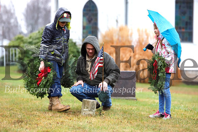 Noah Pallas, 11, lays a wreath on a veteran's grave with his dad Brian and sister Abby, 9, at  St. John's United Methodist Church  cemetary outside of West Sunbury Saturday. Members of West Sunbury Boy Scout and Cub Scout Troup 31, volunteers and veterans were laying wreaths at a number of sites around Butler as part of a National Wreaths Across America Day. Seb Foltz/Butler Eagle