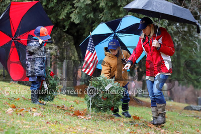 Dylan Waugaman,8, lays a wreath on a veterans grave with his mom Nikki and brother David, 6, at  St. John's United Methodist Church  cemetary outside of West Sunbury Saturday. Members of West Sunbury Boy Scout and Cub Scout Troup 31, volunteers and veterans were laying wreaths at a number of sites around Butler as part of a National Wreaths Across America Day. Seb Foltz/Butler Eagle