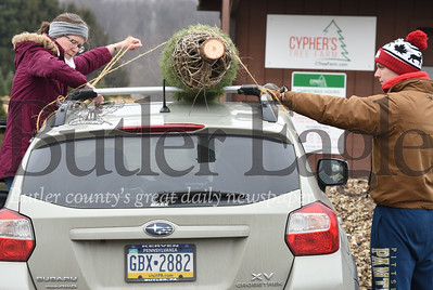 Harold Aughton/Butler Eagle: Amy Lutz of Butler ties an 8 ft. Douglas Fir Christmas tree onto the top of her car with help from her son Josh Lutz, a sophomore biology major at the University of Pittsburgh Monday, Dec. 16, 2019.
