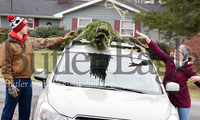 Harold Aughton/Butler Eagle: Josh Lutz, sophomore biology major at the University of Pittsburgh helps his mother, Amy Lutz of Butler a tie a Christmas tree that they purchased at Cypher's Tree Farm in Butler Twp., onto the top of their car Monday, Dec. 16, 2019.