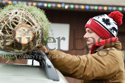 Harold Aughton/Butler Eagle: Josh Lutz, sophomore biology major at the University of Pittsburgh helps his mother, Amy Lutz of Butler load the family Christmas tree onto the top of their car Monday, Dec. 16, 2019.