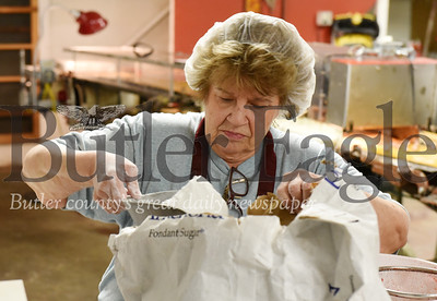 Harold Aughton/Butler Eagle: Treva Mohan spoons out sugar out of a bag to make the filling for Peter's Chocolates.