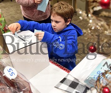 Harold Aughton/Butler Eagle: Jace Steele, 5, of Butler takes a chane on one of the many gift basket drawings at the Butler Health Systems Caring Angel Program basket auction Tuesday, Dec. 17, 2019.