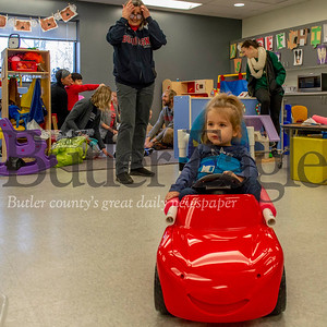 Regina Harbourne, professor of physical therapy at Duquesne University, watches on as Kyla Sayer, 4, of Wexford drives a toy car Thursday at the Easterseals school. The car was repaired by Duquesne's START-Play Hackers, which Harbourne is involved with. Alex J. Weidenhof/Butler Eagle.