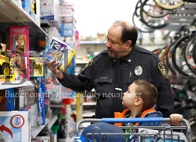 Butler sheriff deputy Mike Smith checks out a toy with his Shop with a Cop child, Traey. Seb Foltz/Butler Eagle