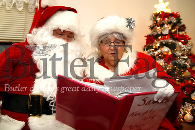 Clad in their Santa and Mrs. Claus garb, Glen Gitzen and his mother Becky read over their real-life 'Naughty and Nice List.' The duo recieve real wish lists of kids prior to some of their events. Seb Foltz/Butler Eagle