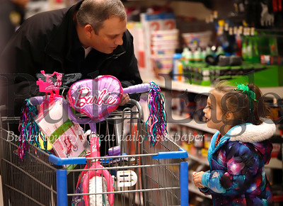 Milania Devanno, 6, consults with detective sergeant Dave Fish shopping for Christmas gifts at Butler Area School District and Butler Walmart's first annual Shop with a Cop event.  Seb Foltz/Butler Eagle