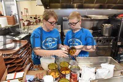 Harold Aughton/Butler Eagle: Angie Popa, and her son, James, 11, volunteered in preparing food for the Salvation Army's Christmas eve meal, Tuesday, December 24, 2019.