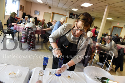 Harold Aughton/Butler Eagle: Nina Ziegler, manager of the Tanglewood Senior Center, pours sparkling grape juice for the seniors gathered to celebrate New Years, Thursday, December 26, 2019.