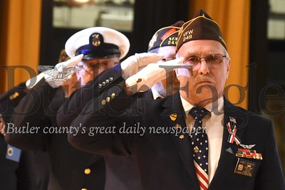 U.S. Army veteran James Bianchi and fellow members of the Butler County Honor Guard salute a Missing Man Table, a ceremony honoring prisoners of war and soldiers missing in action, during a Veterans Day assembly for students at Butler Intermediate High School Friday. Seb Foltz/Butler Eagle