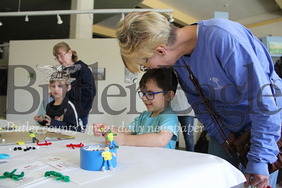 Gunnar Foreback wrangles with a pipe brush cleaner Saturday while his grandmother Christine Myers looks on in Butler's Art Center.
