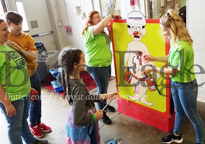 Leah Blank, 11, tries to extract an organ without lighting up the patient's nose during the carnival at Butler Vo-Tech Friday as health occupation class members Jordan Toner, blonde and Paige Hite work the game. PHOTO BY ERIC FREEHLING