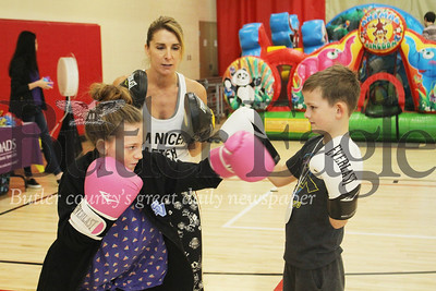 Instructor Lisa Guerrini teaches Sophia and Hunter Tillotson some boxing fundamentals at Healthy Kids day at the YMCA. The Rose E. Schneider Family YMCA will be introducing a youth boxing program this summer. Photo by Caleb Harshberger