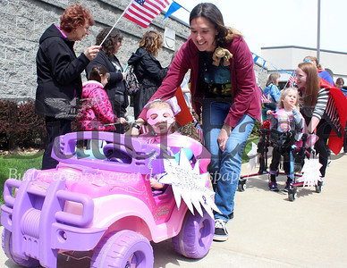 Harold Aughton/Butler Eagle: Kyla Sayer, 4, drives her car with help from Teacher's Assistant Christine Davis, Monday afternoon during the Easterseals Superhero Parade in Cranberry Twp.  Members of the VFW Post 879 colorguard led the parade along with police and ambulance personnel from Cranberry Twp.  The parad was held in recognition of National Autism Awareness Month.