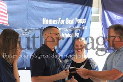 With his wife Jennie (left) U.S. Veteran Justin Hendrickson recieves a 'lucky' horseshoe found during contstruction of his Homes for Troops home. Seb Foltz/Butler Eagle