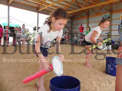 Lilly Nagy, 9, drops her ball into the bucket after balancing it on a pool noodle and paper plate in the Barnyard Olympics at the Butler Farm Show. Photo by Gabriella Canales.