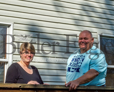 Jodi and Steve Longwell Sr. stand below a bullet hole in the siding of their house they believe to be from the nearby Evans City Sportsman Club. Photo by Alex Weidenhof.