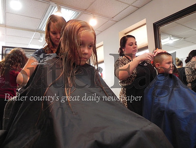 Siblings Zoey, 7, and Dominic Selfridge, 5, get new haircuts from Louis Charles & Co. Head to Toe Salon owner Kris Spreng and salon stylist Corrine Thiel. Photo by Gabriella Canales.