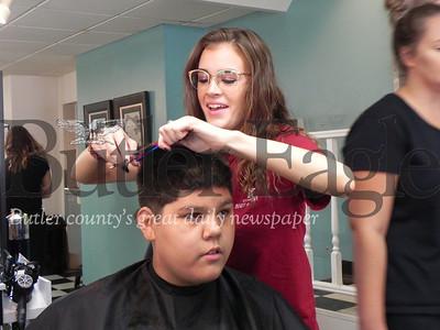 St. Stephens Lutheran School freshman Dartavion Johnson watches as Sammie Oesterling, a Butler Beauty Academy student teacher, cuts his hair. Photo by Gabriella Canales.