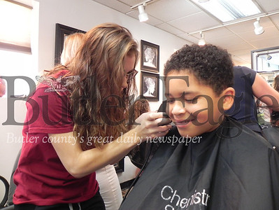 Summit Elementary School second-grader Leonidas Chewe, 8, smiles as Sammie Oesterling, a Butler Beauty Academy student teacher, gives him a fresh haircut at the Butler Beauty Academy at its Back to School Haircuts event organized by the Center for Community Resources. Photo by Gabriella Canales.