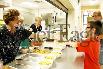 Linda Eury serves up a bowl of chilli to Danny Thompson, 10, at Katie's Kitchen community dinner Thursday. Seb Foltz/Butler Eagle