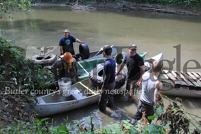 Volunteers during the Connoquenessing Creek cleanup on Saturday bringing their garbage haul to shore.