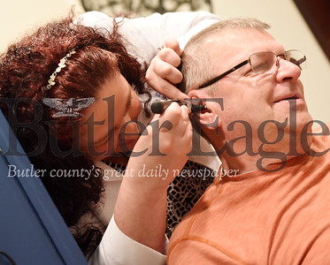 Harold Aughton/Butler Eagle: Kellie Tankersley, owner of Hearing Aide Service by Kellie, prepares for a fitting with her client, Ray Jansen of Evans City, Monday, August 26.