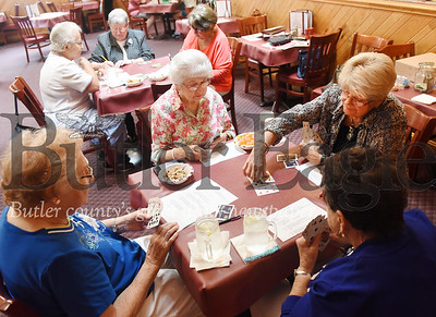 Harold Aughton/Butler Eagle: Pat Fair of Butler picks up the cards on the table during a recent club card meeting at Mama Rosa's. The club has been meeting since 1957.