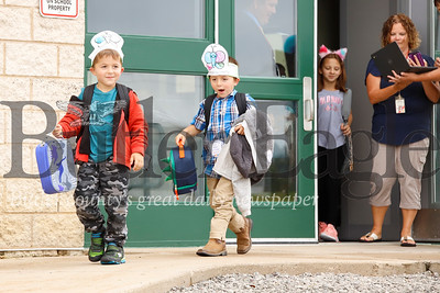Twins Ethan, 6,(left) and Evan Brewer head down the ramp followed by their sister Emma to greet their mom, Sara Brewer, after being released from Dassa McKinney Elementary School in Moniteau School District Tuesday. Seb Foltz/Butler Eagle