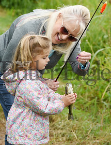 Harold Aughton/Butler Eagle: Kaitlyn Taylor, 5, spent her last day of summer break with her sister, Hailey, 7, and grandparents, Paul and Brenda Bordas of Butler fishing at Glade Run Lake. Kaitlyn checks out the largemouth bass she reeled in with her grandmother Brenda.