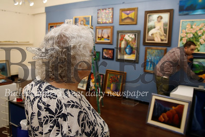 Local artist and volunteer Sonja Barnes watches and gives feedback to Butler Arts Center gallery director Stephen Haley hanging paintings Tuesday evening in preparation for Friday's exhibit opening. Seb Foltz/Butler Eagle