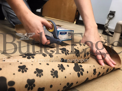 Kennel assistant Bri Murphy, 20, cut wrapping paper to finish making homemade dog treats at the Butler County Humane Society. Murphy said she gives her pet special hone treats on Valentine's Day.