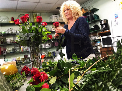 Tina Barger, a floral designer at Bortmas, the Butler Florist, prepares a dozen rose floral arrangement for Valentine's Day.