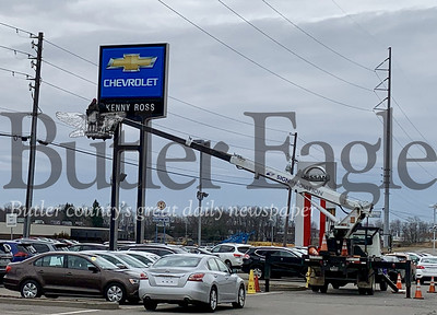 Photos by Alexandria Mansfield. Crews replace Kenny Ross signs with #1 Cochran after the company acquired its Chevrolet and Nissan locations in Zelienople.
