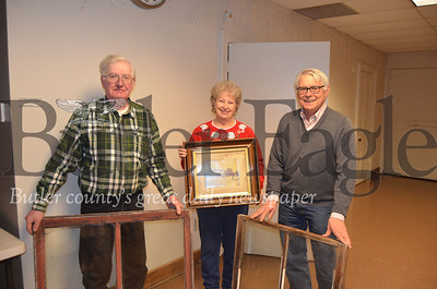 Glenn Studebaker (left) poses with his wife, Pearl (middle), and Historic Harmony President Rodney Gasch (right). They hold the old windows from the Studebakers' house, built sometime between the 1820s and 1830s, and one of the first photos of the house. The couple donated the windows to the Historic Harmonywindow restoration project at the Wagner Haus.Pics by Alexandria Mansfield.