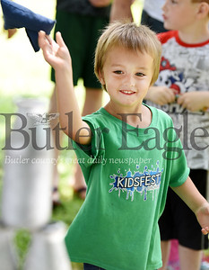 Harold Aughton/Butler Eagle: Grace Scott,4, of Butler attempts to knock down the bottles during the carnival held at Rotary Park, Friday, June 28.