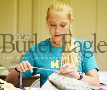 Harold Aughton/Butler Eagle: Alivia Miller, 13, of Mars puts the draw string in the homemade bags at teh Holy Sepulcher Church, Monday, July 1.