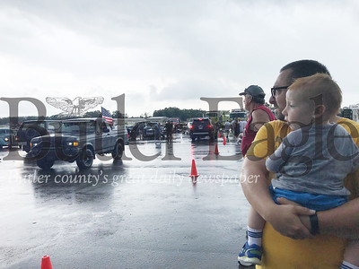 Matt Gorski of Valencia and his 2-year-old son Shane watch cars come and go in the rain during Saturday's 19th annual Mega Cruise. Photo by Gabriella Canales.