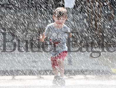 Harold Aughton/Butler Eagle: Beckett Reddick, 4, of Mars skips through water compliments of the Butler firefighters during the Stuff A Bus event sponsored by teh Golden Tornado Scholastic Foundation Tuesday, July 9 at the YMCA.
