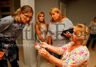 Jean Vincent of the Psychic Vincent Sisters holds up a recording device and spirit detector for Kate Shereirman to speak into. Shereirman asked if the spirit of her mother is present. Seb Foltz/Butler Eagle
