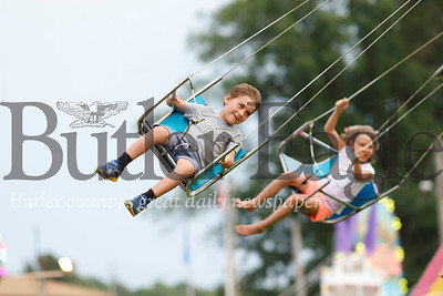 Townes Gaston, 6, goes for a spin around the swings at the Saxonburg Carnival Tuesday night. Seb Foltz/Butler Eagle